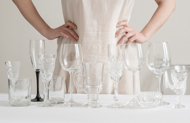 Женские руки с разными бокалами на столе на белом