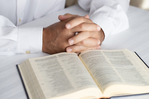 開いている聖書のプレーヤーの手のクローズ。背景を祈る男。