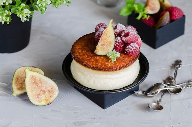 ベリーをトッピングしたクリーミーなニューヨークスタイルのチーズケーキ。フルーツ、イチジク、ラズベリー、ミントを使ったエレガントなフードスタイリングの例。