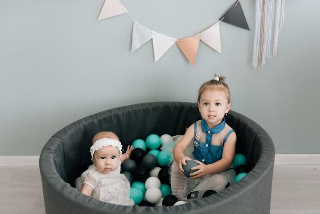 Маленькая девочка в дошкольном возрасте и ее сестра играют в бассейне с разноцветными пластиковыми шариками