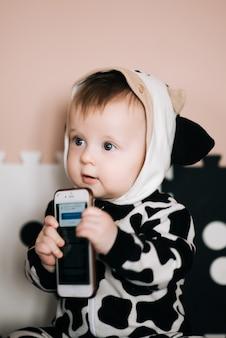 Ребенок кусает чехол для смартфона. очаровательный младенец грызет смартфон в защитном чехле.