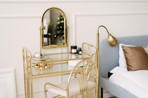 美しい白いインテリア。スタッコ付きクラシックルームライトウォール、ガラス、装飾、セレクティブフォーカスで飾られたガラスの黄金の椅子ドレッシングテーブル