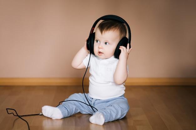 音楽を聞くヘッドフォンで遊んで家の床に座っているかわいい若い赤ちゃん