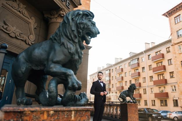 Красивый стильный мужчина жених ждет его невеста в городе европы. свадебная концепция