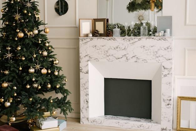 クリスマスと新年の装飾。クリスマスツリー、暖炉、お祝いテーブル付きのリビングルーム