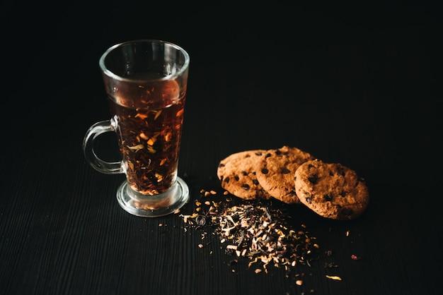 チョコレートチップとオートミールクッキー。黒い壁にお茶を一杯とクッキー