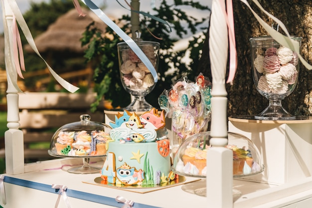 あなたの誕生日のためのキャンディーバー。自然の中でパステルカラーの子供たちのパーティー。美しい甘いケーキ、ハンドマシュマロ、カップケーキ、ロリポップ、メレンゲ。
