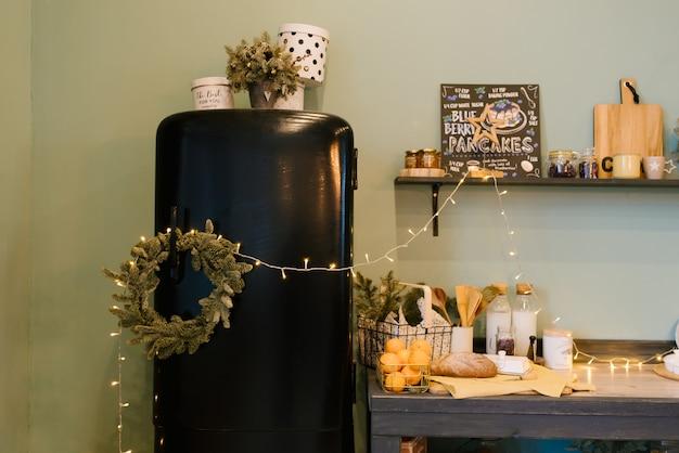 クリスマスと新年の装飾。黒いレトロな冷蔵庫付きのキッチン