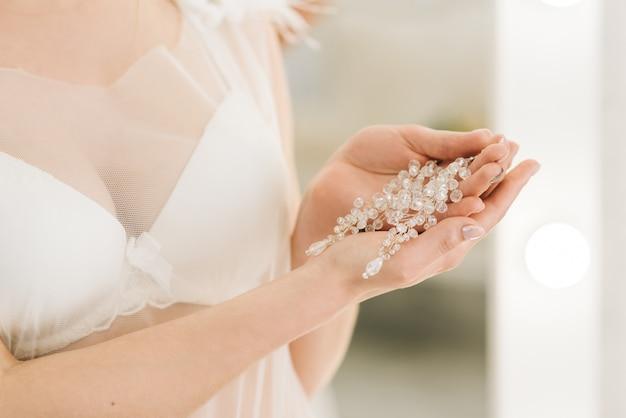 セレクティブフォーカス、花嫁の手の中の女性のウェディングジュエリー(イヤリング)