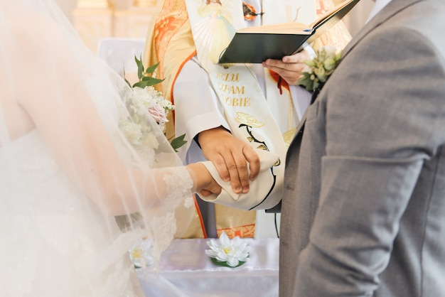 Руки жениха и невесты и священника крупным планом. таинство свадьбы в церкви