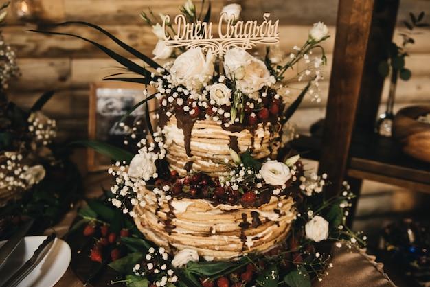 花で飾られた白い裸のケーキ、結婚式、誕生日、イベントのための素朴なスタイル。