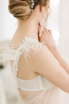 結婚式の日の詳細。羽のクローズアップと花嫁のドレスのガウン