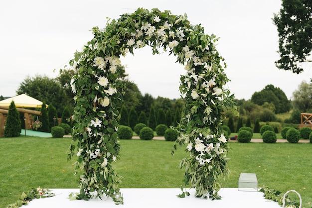 結婚式のアーチ。美しい生花と布で飾られたアーチ。結婚場所での登録。
