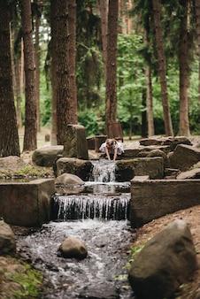緑の森のストリームで手を洗う女の子