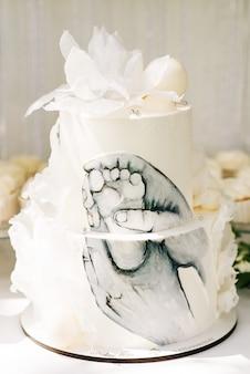 キャンディーバー。子供の足の写真が美しい白いケーキ、子供の誕生日パーティーのコンセプト