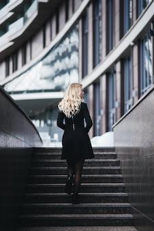黒のドレスで金髪のウェーブのかかった髪の美しい少女はモダンな建物に反対します。