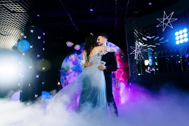 美しい光とアトスを伴う濃い煙の素晴らしい最初の結婚式のダンス。空間のスタイルで装飾。宇宙ウェディング