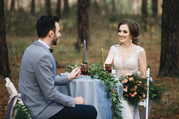 Жених и невеста сидят за столом на двоих в лесу. они улыбаются и пьют глинтвейн. осень. концепция романтического свидания