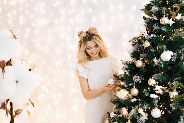白い髪の美しい少女のクリスマスの肖像画。クリスマスツリーを飾る魅力的な女性