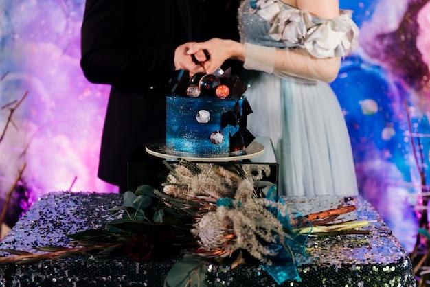 Космическая пара разрезает свадебный торт, украшенный шоколадом и планетами. концепция праздничных десертов к празднику