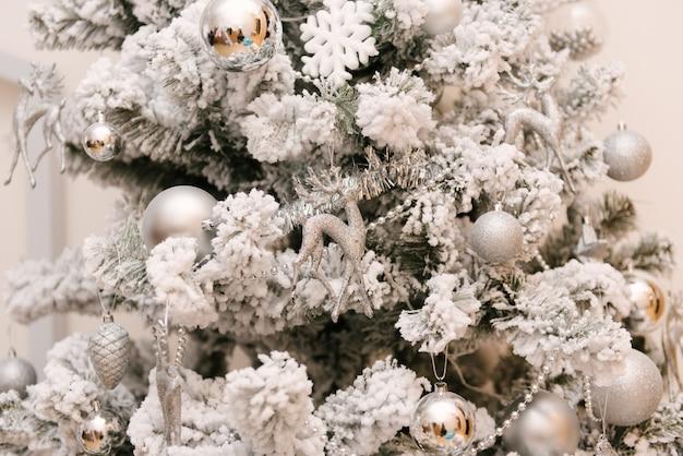 雪に覆われた白いクリスマスツリーと銀のおもちゃと鹿、セレクティブフォーカス