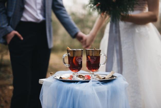Два бокала глинтвейна стоят в лесу на фоне молодоженов. осень. концепция романтического свидания. выборочный фокус