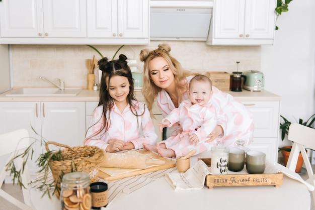 Счастливая любящая семья готовит пекарню вместе. мать и две дочери девочки готовят печенье и веселятся на кухне. домашняя еда и маленький помощник.