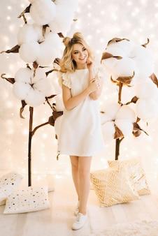 白い髪の美しい少女のクリスマスの肖像画。綿の大きな枝の間で魅力的な女性