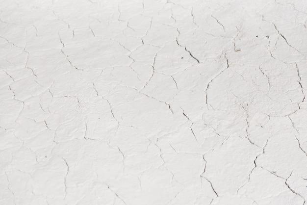 白ひび割れ背景テクスチャ、暗いスクラッチで明るい背景、チョークの採石場近くの地面、コピースペース