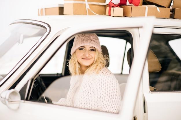 女の子はクリスマスツリーで飾られたレトロな車に乗ってプレゼント