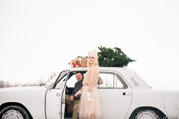 男と女がクリスマスツリーで飾られたレトロな車に乗る