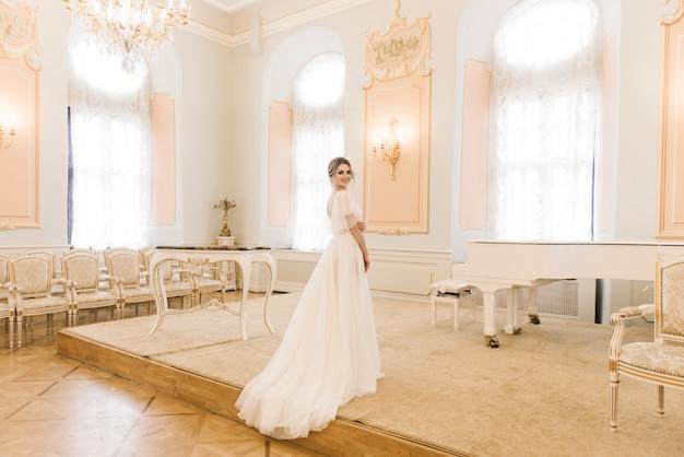 Портрет красивой невесты рядом с пианино в роскошном интерьере