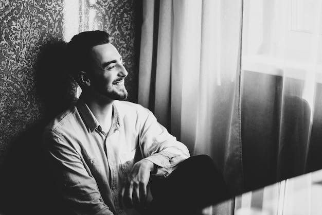 Стильный жених в белой рубашке и галстуке-бабочке позирует в окно света. уверенный и счастливый портрет человека. жених готовится утром. креативное свадебное фото