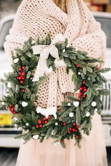 ノビリスのスタイリッシュなクリスマスリースは、赤い果実、白いおもちゃ、レトロな車の背景に女の子の手で弓で飾られました。セレクティブフォーカス