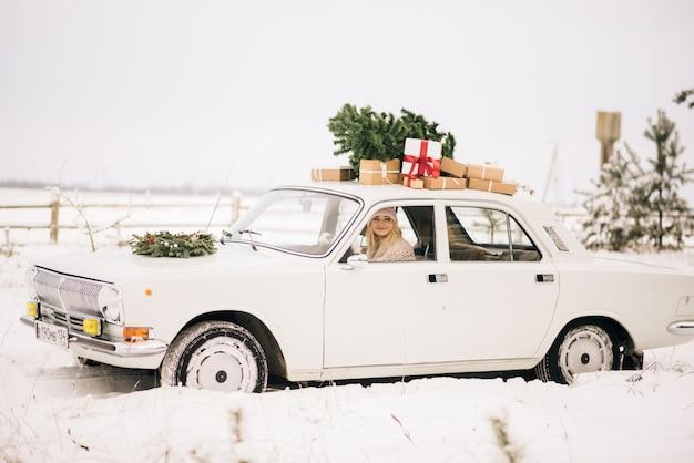 女の子は、クリスマスツリーで飾られたレトロな車に乗って、雪に覆われた森にプレゼントします。冬のクリスマス写真撮影のコンセプト