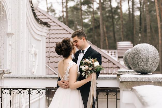 美しいホテルのバルコニーで新郎新婦の幸せな若い恋人の肖像画。結婚式の日