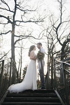 Счастливый молодой жених и невеста, стоя на лестнице висячий мост против солнца. свадебная фотография