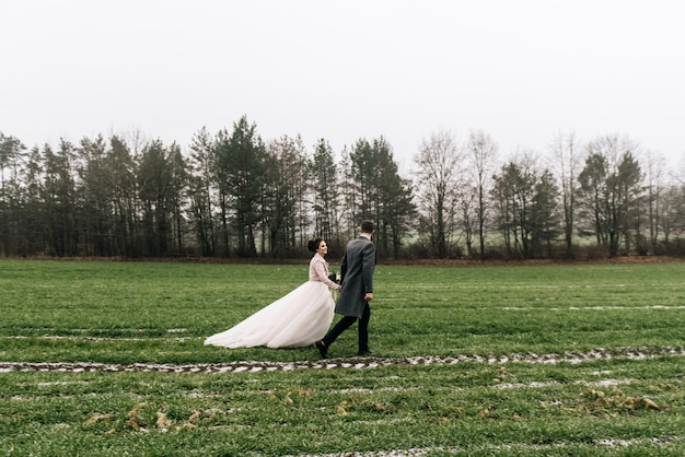 Портрет счастливых молодых любящих молодоженов. жених и невеста бегут по полю с первым снегом. день свадьбы