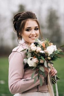 Красивый портрет невесты в стильном платье с зимним букетом роз, хлопка и ели на зеленом поле с первым. свадебная фотография