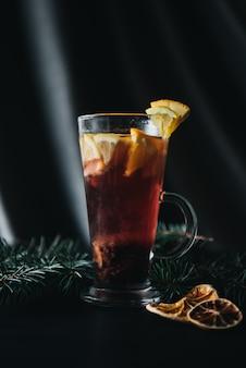 伝統的な冬と秋のドリンク。クリスマスと感謝祭のカクテル。オレンジ、リンゴ、ローズマリー、シナモン、暗い石の背景にスパイスとホットワインのコピースペース平面図