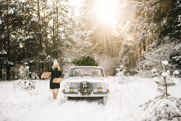 女の子はクリスマスの準備をしていて、冬の雪に覆われた森の中のレトロな車の屋根にクリスマスツリーとプレゼントを読み込みます
