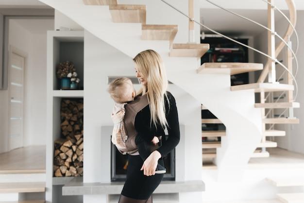 Стильная молодая мама держит в эрго рюкзаке своего милого годовалого ребенка дома в красивом интерьере. удобство для мамы.