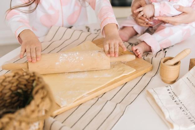 Счастливая любящая семья готовит пекарню вместе. мать и две дочери - девушка, которая готовит печенье и веселится на кухне. домашняя еда и маленький помощник. крупный план, выборочный фокус