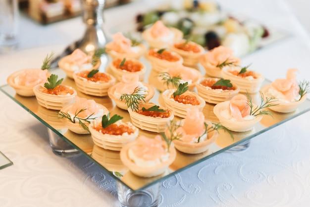 Красиво оформленный ресторанный банкетный стол с салатами и холодными закусками. разнообразие вкусных вкусных закусок на столе