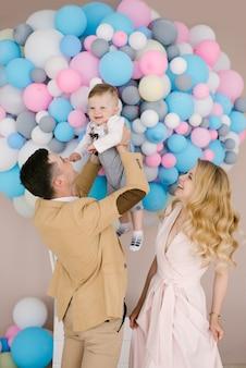 Красивые молодые родители улыбаются с годовалого ребенка на фоне розовые и голубые шары.