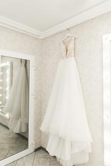 鏡に掛かっているウェディングドレス、花嫁の朝