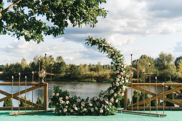 結婚式のアーチ。三日月の形をした美しい生花で飾られたアーチ