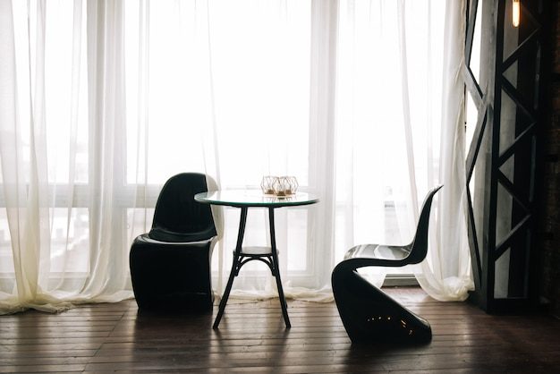 テーブルと珍しい黒い椅子が窓、キッチンインテリア、ロマンチックな背景の上に立つ