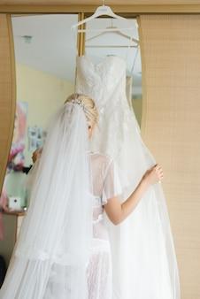 結婚式の日の詳細。花嫁は彼女のウェディングドレスを調整します