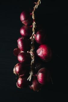暗い背景に赤玉ねぎの種類。新鮮な有機野菜。食品と料理のコンセプトです。サラダ、スープ、料理の材料。